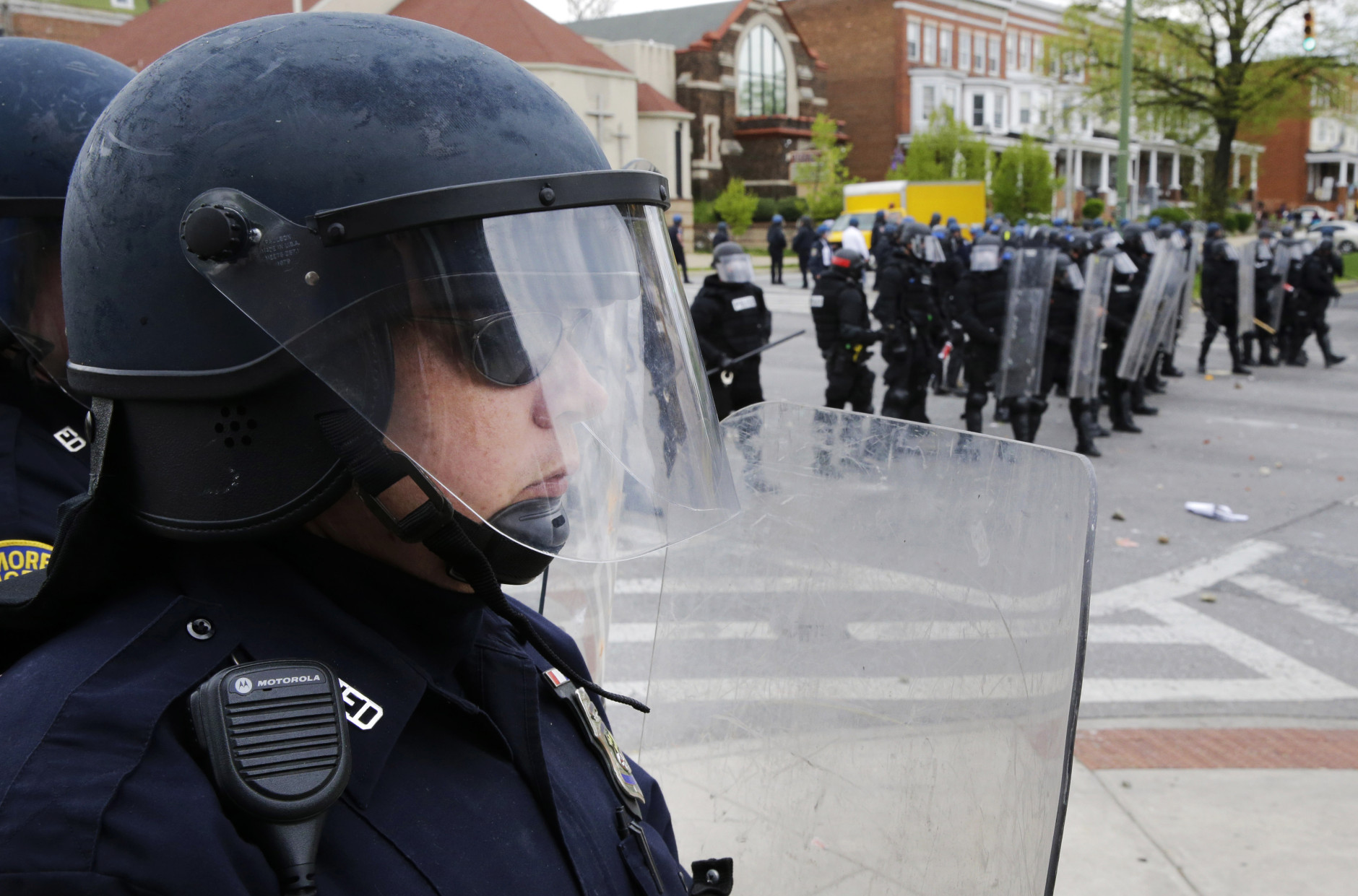Police stand in formation in response to demonstrators who were throwing objects at police, Monday, April 27, 2015, after the funeral of Freddie Gray in Baltimore. Gray died from spinal injuries about a week after he was arrested and transported in a Baltimore Police Department van. (AP Photo/Patrick Semansky)