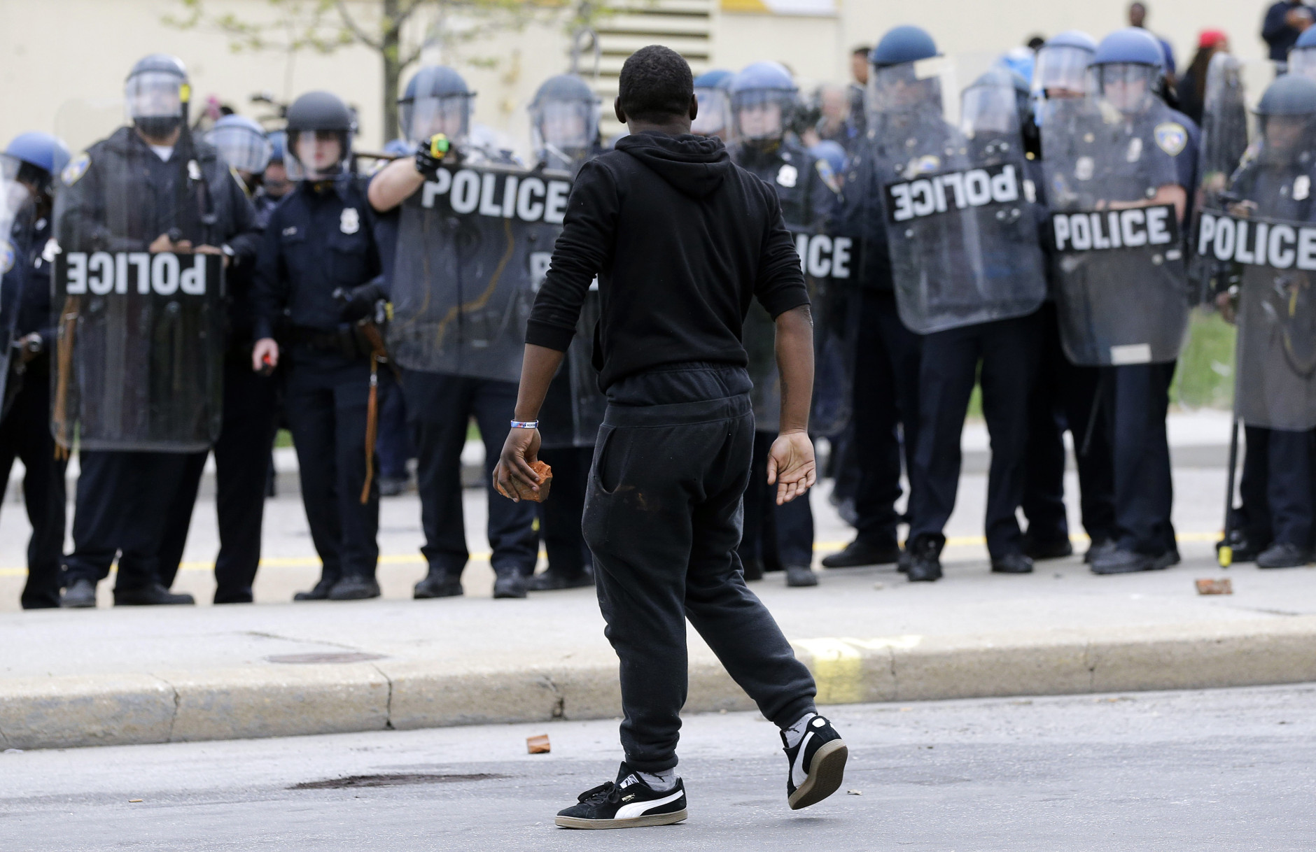 A demonstrator walks past police with a brick as they respond to thrown objects, Monday, April 27, 2015, after the funeral of Freddie Gray in Baltimore. Gray died from spinal injuries about a week after he was arrested and transported in a Baltimore Police Department van. (AP Photo/Patrick Semansky)