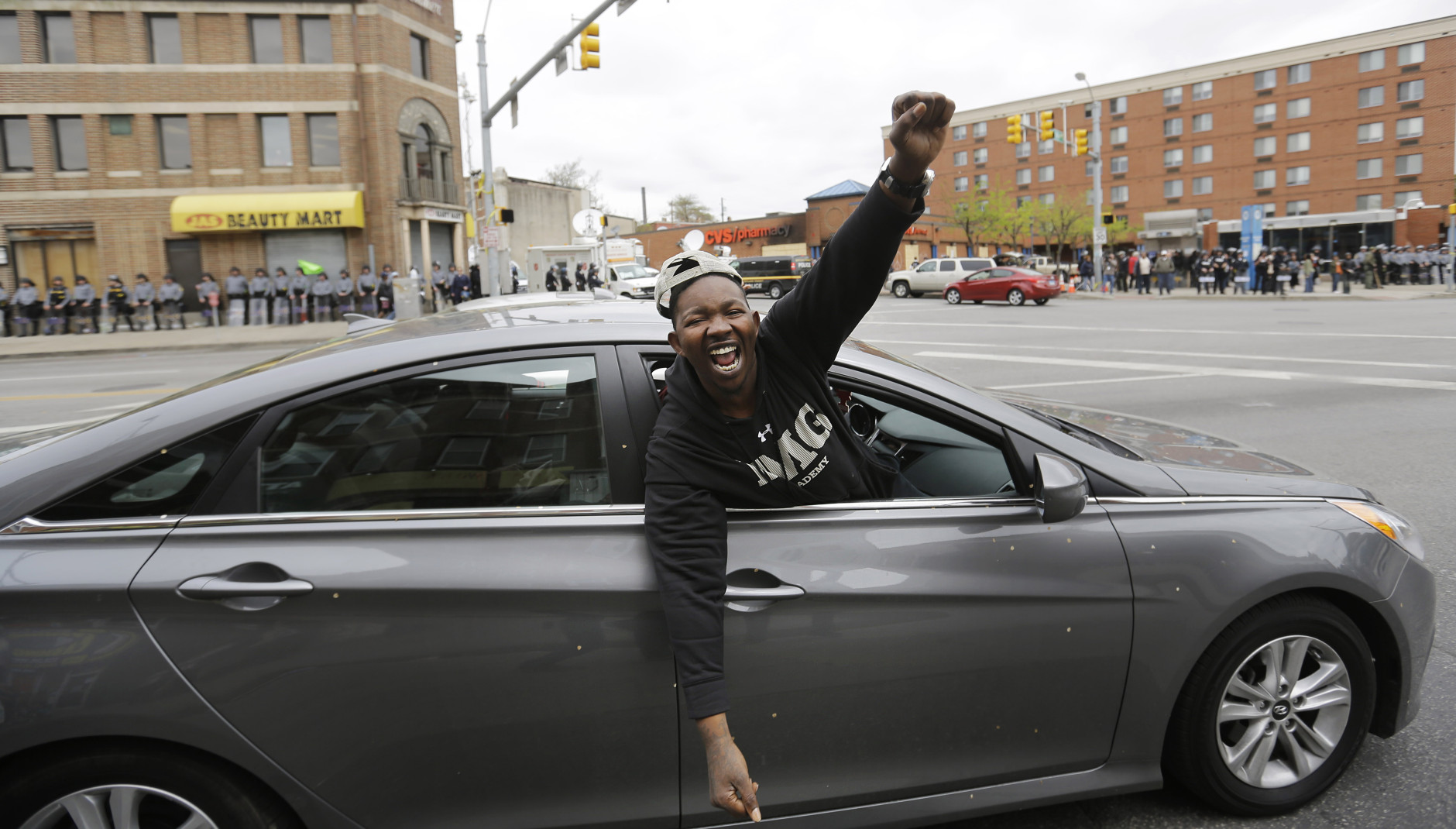 A passing motorist celebrates in the intersection where some of Monday's riots occurred on Friday, May 1, 2015, after State's Attorney Marilyn J. Mosby announced criminal charges against all six officers suspended after Freddie Gray suffered a fatal spinal injury while in police custody in Baltimore.  Mosby announced the stiffest charge, second-degree depraved heart murder, against the driver of the police van. Other officers faced charges of involuntary manslaughter, assault and illegal arrest.  (AP Photo/David Goldman)