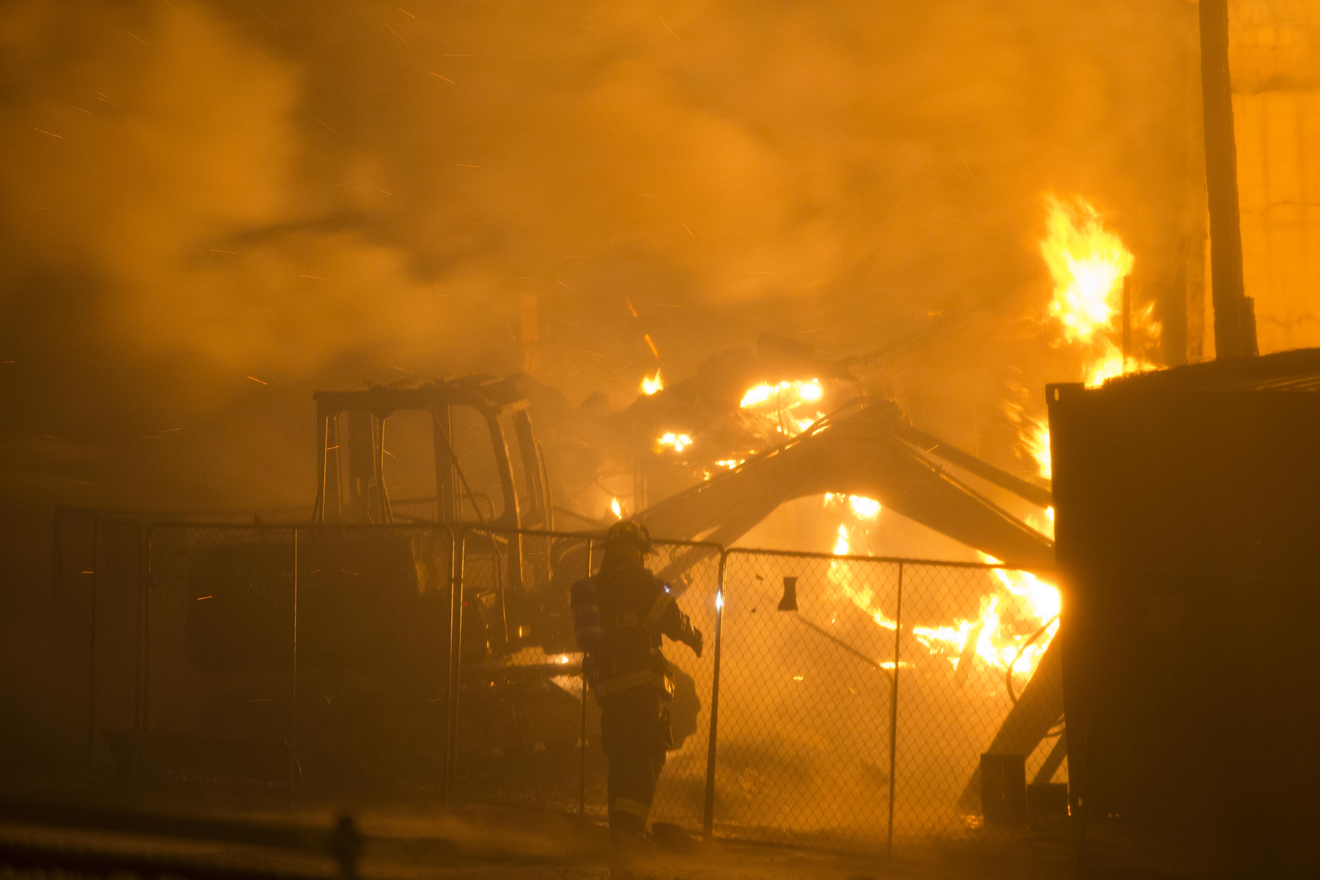 Firefighters battle a blaze, Monday, April 27, 2015, after rioters plunged part of Baltimore into chaos, torching a pharmacy, setting police cars ablaze and throwing bricks at officers. (AP Photo/Matt Rourke)