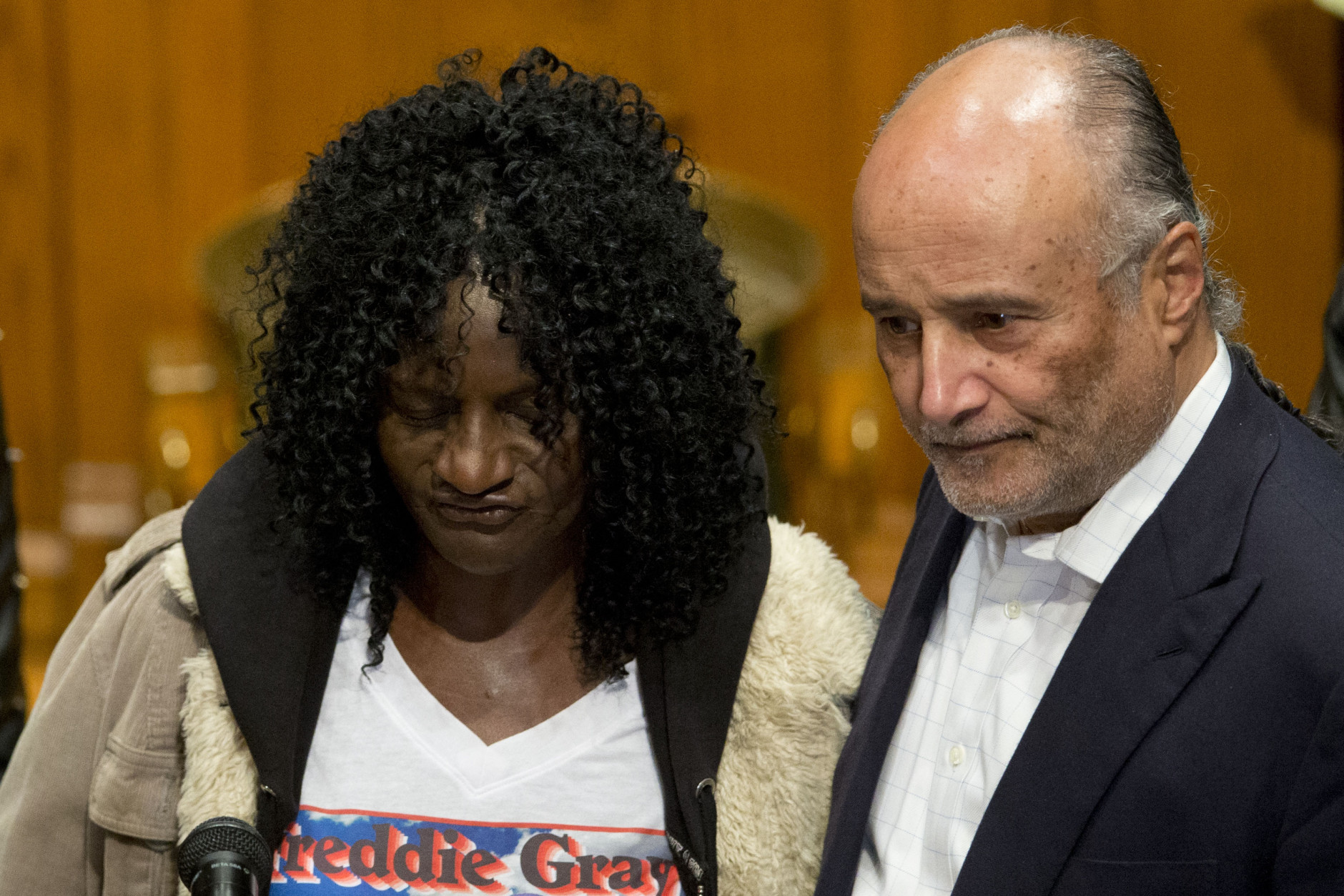 Gloria Darden, left, mother of Freddie Gray, gathers with family attorney Billy Murphy and clergy for a news conference, Monday, April 27, 2015, in Baltimore. Rioters plunged part of Baltimore into chaos torching a pharmacy, setting police cars ablaze and throwing bricks at officers. (AP Photo/Matt Rourke)