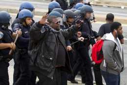 Baltimore police officers push back demonstrators who are throwing rocks at the police, after the funeral of Freddie Gray, on Monday, April 27, 2015, at New Shiloh Baptist Church in Baltimore. Gray died from spinal injuries about a week after he was arrested and transported in a Baltimore Police Department van.  (AP Photo/Jose Luis Magana)