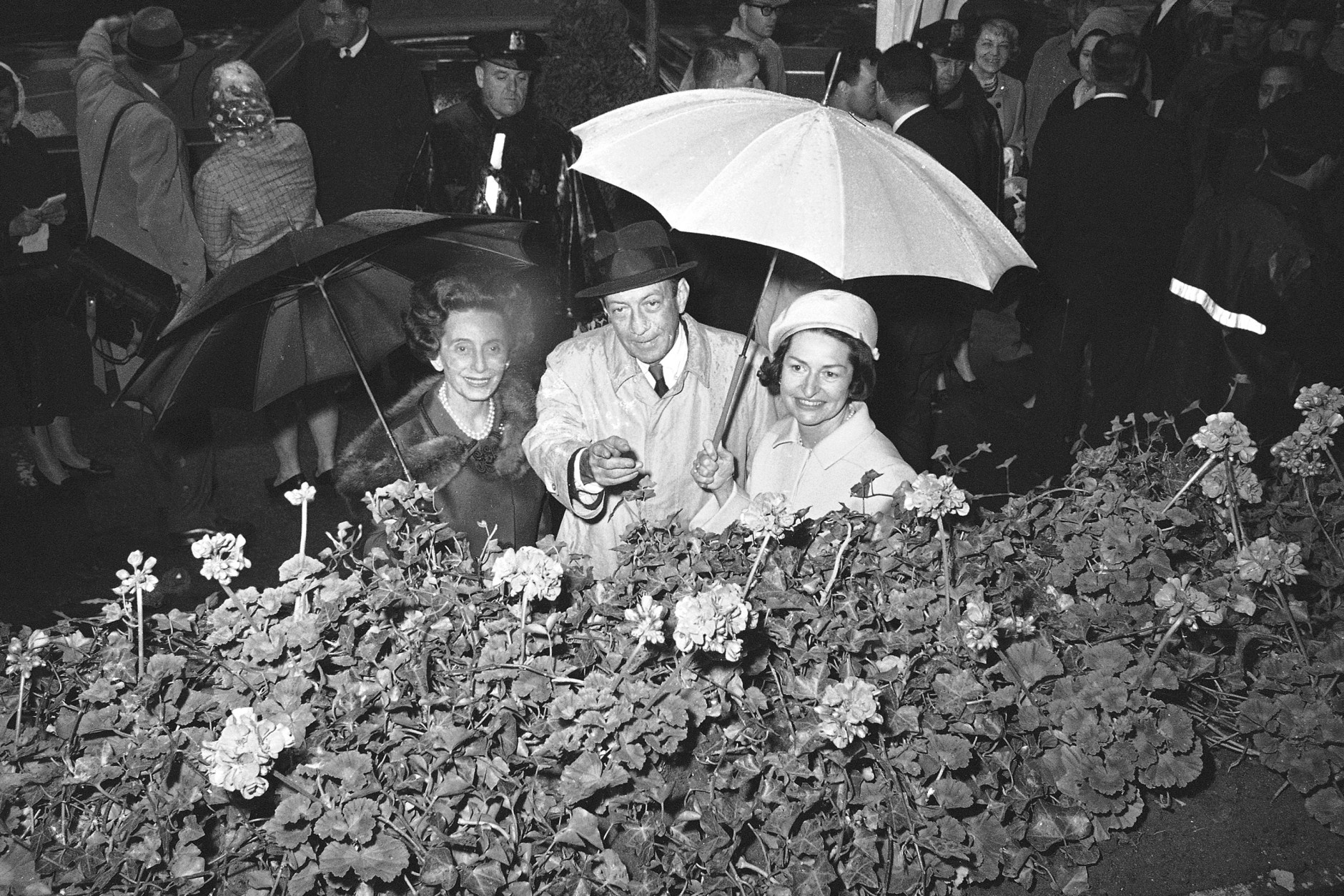 """Lady Bird Johnson, wife of Pres. Johnson, uses an umbrella to keep dry as she and New York's Mayor Robert F. Wagner, center, with Anna Rosenberg Hoffman, left, co-chairman of the city's """"Salute to Season"""" program, inspect a flower display at the Plaza Hotel in New York, May 7, 1965.  The nation's first lady called upon New Yorkers to use green thumbs in beautifying the city's streets.  (AP Photo/John Lent)"""