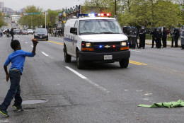 A boy throws a brick at a police van, Monday, April 27, 2015, during a skirmish between demonstrators and police after the funeral of Freddie Gray in Baltimore. Gray died from spinal injuries about a week after he was arrested and transported in a Baltimore Police Department van. (AP Photo/Patrick Semansky)