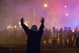 A protestor faces police enforcing a curfew Tuesday, April 28, 2015, in Baltimore. A line of police behind riot shields hurled smoke grenades and fired pepper balls at dozens of protesters to enforce a citywide curfew. (AP Photo/Matt Rourke)