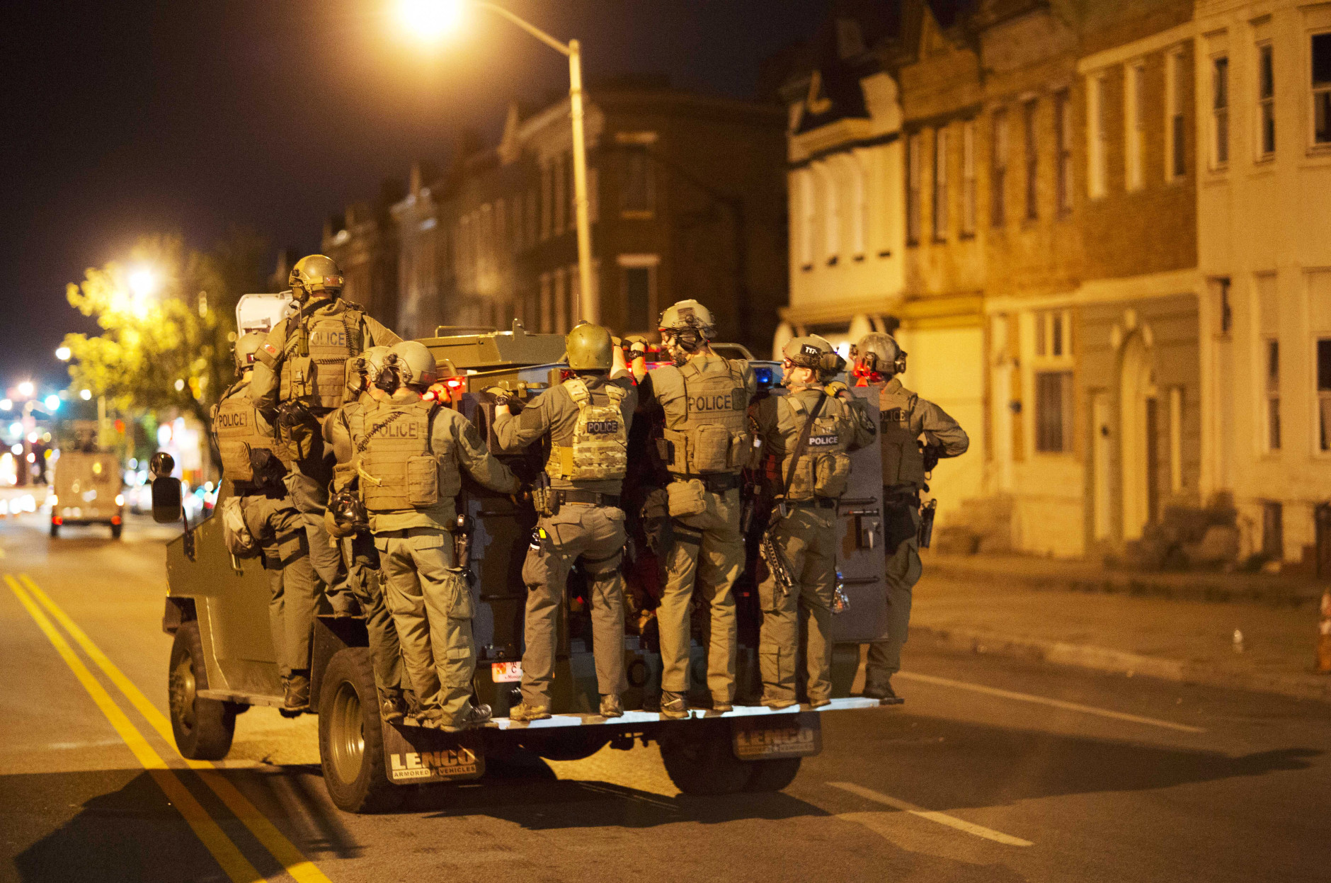Police ride on an armored vehicle through the area where Monday's riots occurred following the funeral for Freddie Gray, after a 10 p.m. curfew went into effect, Tuesday, April 28, 2015, in Baltimore. (AP Photo/David Goldman)