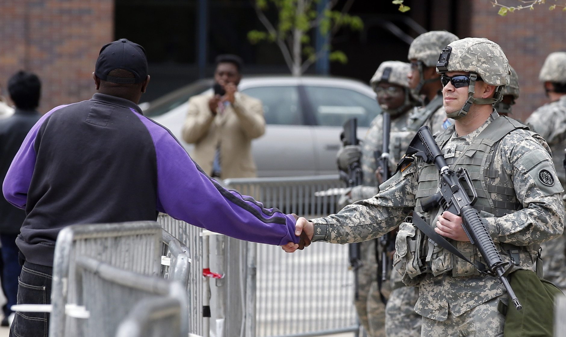 A man shakes hands with a National Guard soldier outside City Hall, Friday, May 1, 2015 in Baltimore. State's Attorney Marilyn J. Mosby announced criminal charges Friday,  against all six officers suspended after Freddie Gray suffered a fatal spinal injury in police custody. Mosby announced the stiffest charge, second-degree depraved heart murder,  against the driver of the police van. Other officers faced charges of involuntary manslaughter, assault and illegal arrest.  (AP Photo/Alex Brandon)