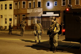 Police shine a light into a window as they enforce curfew, Tuesday, April 28, 2015, in Baltimore, a day after unrest that occurred following Freddie Gray's funeral. (AP Photo/Patrick Semansky)