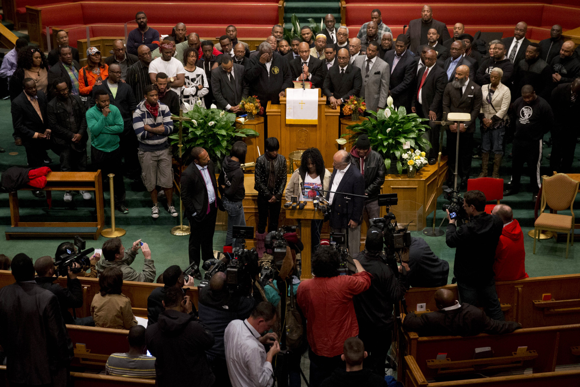 Gloria Darden, mother of Freddie Gray, speaks behind the podium with family members and clergy for a news conference, Monday, April 27, 2015, in Baltimore. Rioters plunged part of Baltimore into chaos torching a pharmacy, setting police cars ablaze and throwing bricks at officers. (AP Photo/Matt Rourke)