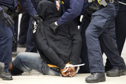 Baltimore police officers detain a demonstrator after clashes with police, after the funeral of Freddie Gray, on Monday, April 27, 2015, at New Shiloh Baptist Church in Baltimore. Gray died from spinal injuries about a week after he was arrested and transported in a Baltimore Police Department van. (AP Photo/Jose Luis Magana)