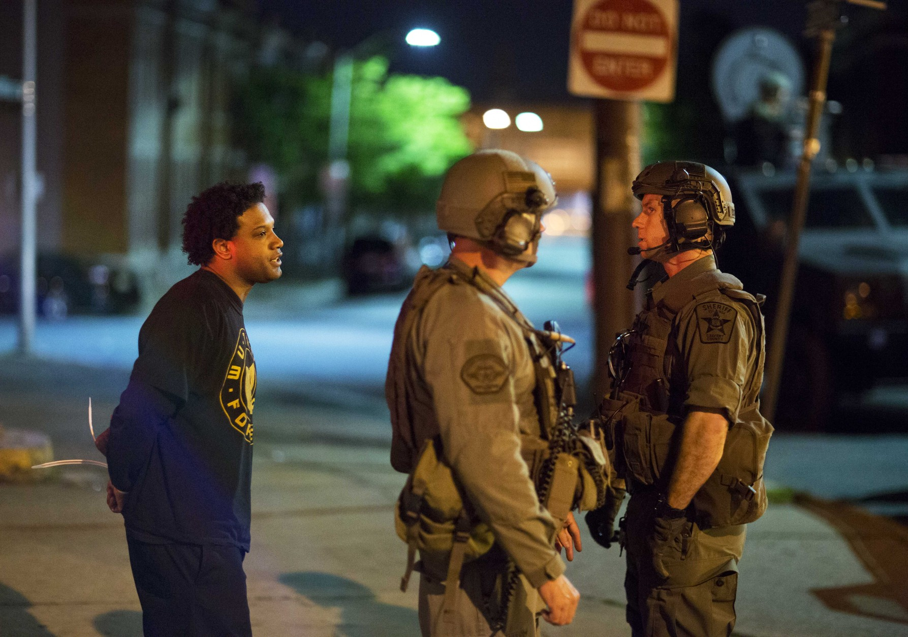 A man at left who would not give his name is arrested for violating the curfew where Monday's riots occurred following the funeral for Freddie Gray, Tuesday, April 28, 2015, in Baltimore. (AP Photo/David Goldman)