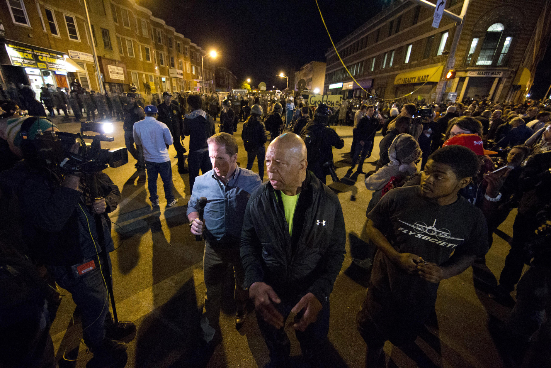 U.S. Rep. Elijah Cummings, D-Md., asks people to go home after the 10 p.m. curfew Tuesday, April 28, 2015, in Baltimore. A line of police behind riot shields hurled smoke grenades and fired pepper balls at dozens of protesters to enforce a citywide curfew. (AP Photo/Matt Rourke)