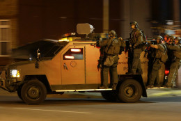 Montgomery County Police ride on an armored vehicle as they enforce curfew, Tuesday, April 28, 2015, in Baltimore, a day after unrest that occurred following Freddie Gray's funeral. (AP Photo/Patrick Semansky)