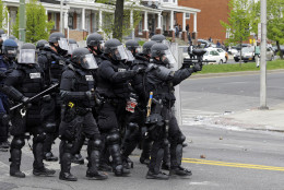 Police move down a street in response to demonstrators who were throwing objects, Monday, April 27, 2015, after the funeral of Freddie Gray in Baltimore. Gray died from spinal injuries about a week after he was arrested and transported in a Baltimore Police Department van. (AP Photo/Patrick Semansky)
