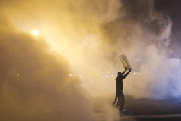 A protestor holds a sign surrounded by smoke Tuesday, April 28, 2015, in Baltimore. A line of police behind riot shields hurled smoke grenades and fired pepper balls at dozens of protesters Tuesday night to enforce a citywide curfew, imposed after the worst outbreak of rioting in Baltimore since 1968. (AP Photo/Matt Rourke)