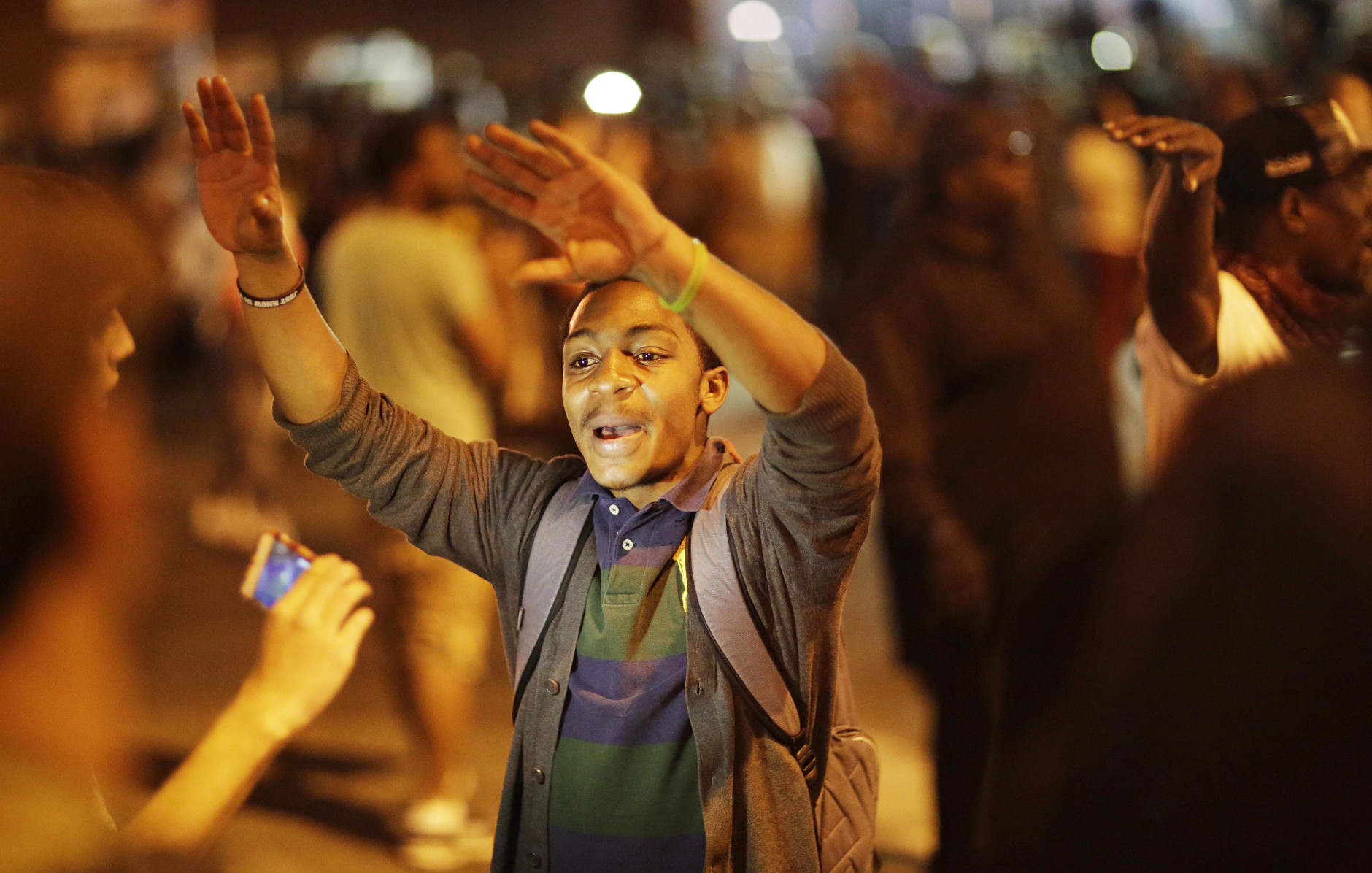 A man asks the crowd to back up in front of a line of police officers in riot gear as part of a community effort to disperse the crowd ahead of a 10 p.m. curfew in the wake of Monday's riots following the funeral for Freddie Gray, Tuesday, April 28, 2015, in Baltimore. (AP Photo/David Goldman)