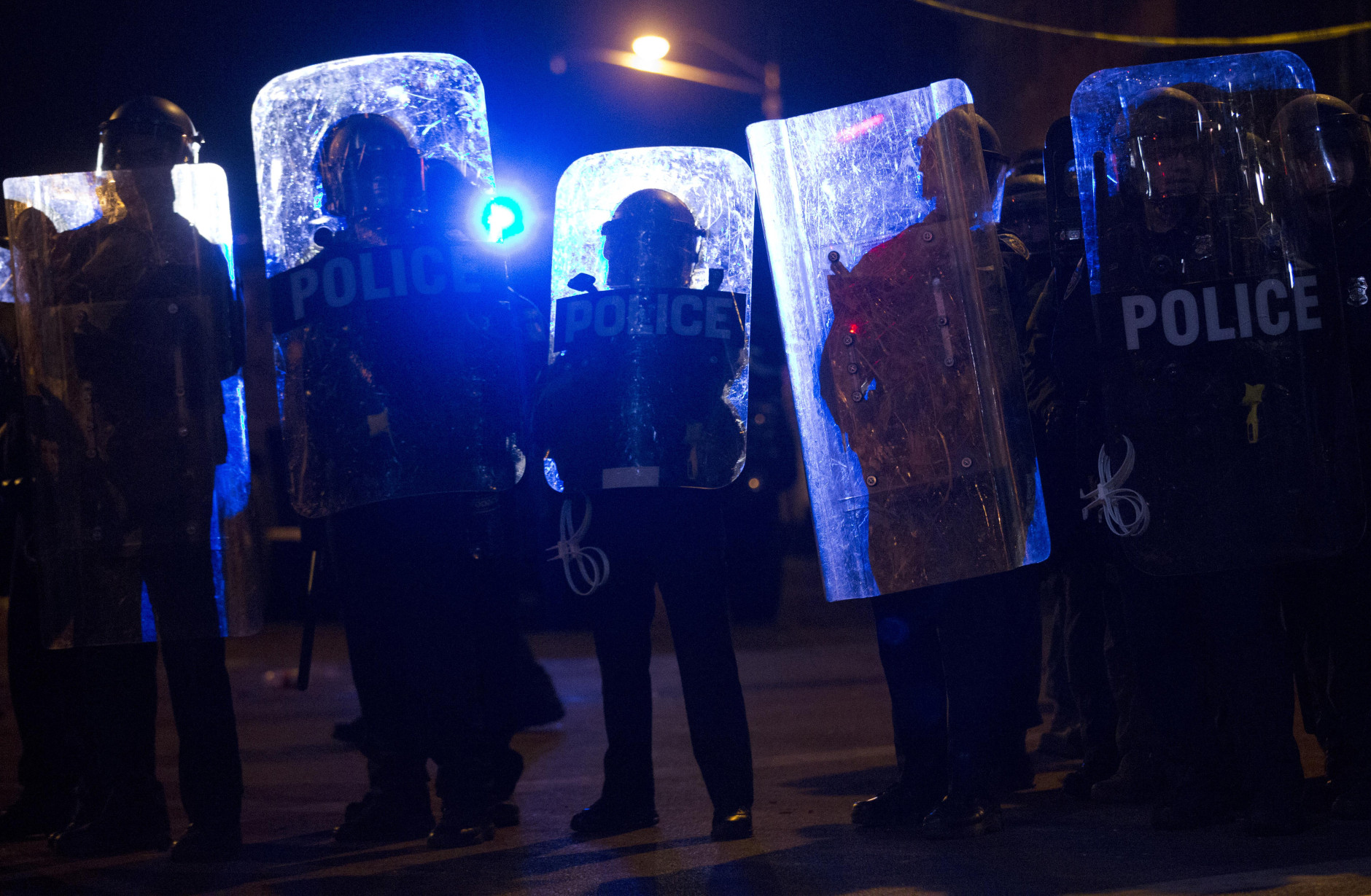 Police advance after the start of a curfew Tuesday, April 28, 2015, in Baltimore. A line of police behind riot shields hurled smoke grenades and fired pepper balls at dozens of protesters to enforce a citywide curfew. (AP Photo/Matt Rourke)