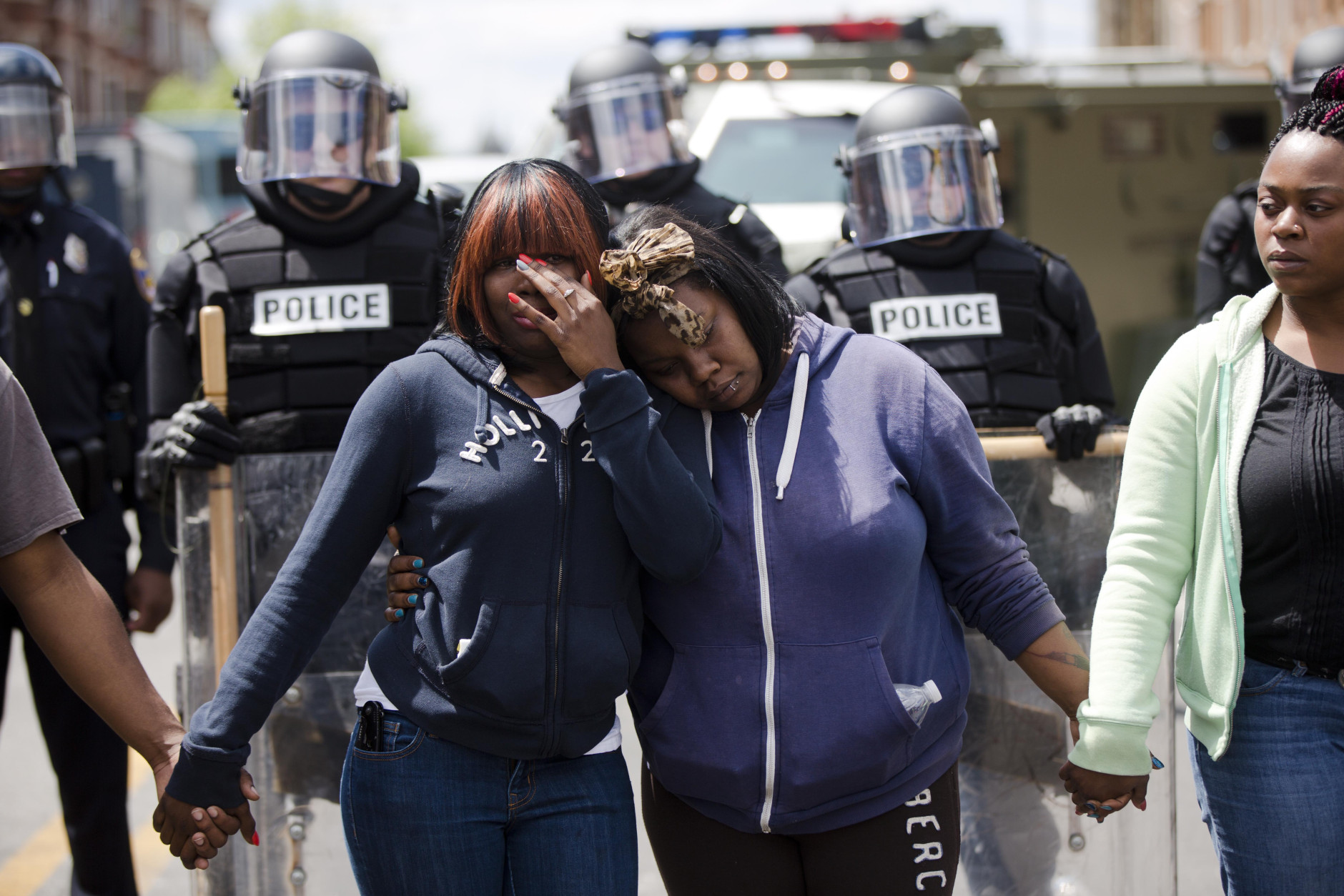 Jerrie Mckenny, center left, and her sister, Tia Sexton embrace as people sing the hymn Amazing Grace Tuesday, April 28, 2015, in Baltimore, in the aftermath of rioting following Monday's funeral for Freddie Gray, who died in police custody. The streets were largely calm in the morning and into the afternoon, but authorities remained on edge against the possibility of another outbreak of looting, vandalism and arson.  (AP Photo/Matt Rourke)