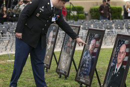 Purple Heart recipient Pfc. James Armstrong, touches the image of Cpt. John Gaffaney, as he looks at pictures of those killed in the 2009 Fort Hood shooting prior to a Purple Heart ceremony held at Fort Hood, Texas, on Friday, April 10, 2015.  Survivors and family members of those killed during the attack by Maj. Nidal Hasan in the 2009 Fort Hood shooting were awarded 44 medals, Purple Heart for soldiers and Defense of Freedom Medals for civilians. (AP Photo/Austin American-Statesman, Rodolfo Gonzalez, Pool)