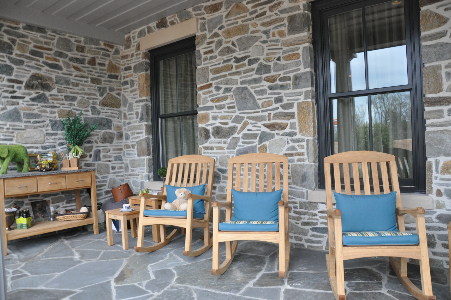 The front porch of the DC Design House was styled by Nicolette Powell and John Lemieux of Country Casual. The natural furniture against the stone facade creates an inviting welcome for visitors. (WTOP/Rachel Nania)