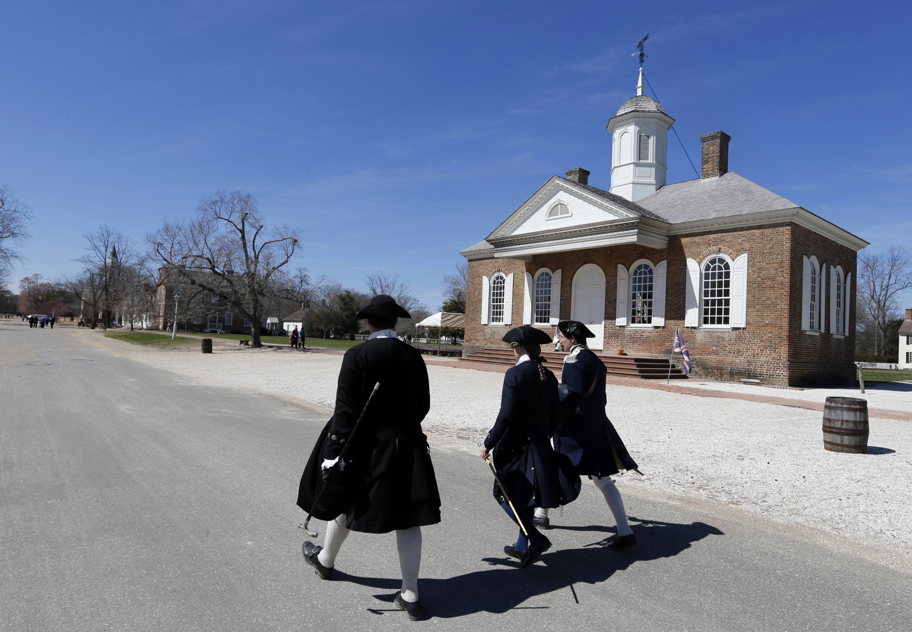 ADVANCE FOR SUNDAY, APRIL 19 AND THEREAFTER - In this photo taken March 18, 2015, actor/interpreters walk in front of the Colonial courthouse along Duke of Gloucester street in the Colonial Williamsburg area of Williamsburg, Va. John Hinckley, the last man to shoot an American president now spends most of the year in a house overlooking the 13th hole of a golf course in a gated community in Williamsburg. An almost three-hour drive south of Hinckley's institutional home of St. Elizabeths Hospital in the nation's capital, Williamsburg is both a tourist destination and a retirement mecca.  (AP Photo/ Steve Helber)