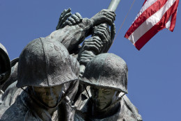 An American flag flies over the U.S. Marine Corps Memorial in Arlington, Va., Wednesday, April 29, 2015. The famous bronze U.S. Marine Corps War Memorial overlooking Washington that depicts Marines raising the American flag at Iwo Jima during World War II has begun turning green with age but now will be restored with a $5.37 million gift. Philanthropist David Rubenstein announced Wednesday that he will give the National Park Foundation the funds needed to wash, wax and restore the memorial and its plaza and landscaping. Improvements are also planned for the memorial's signage and access for handicapped visitors. The project will also restore the memorial's engravings to be much brighter. (AP Photo/Jacquelyn Martin)