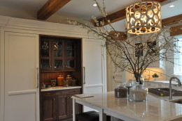 The kitchen features custom cabinetry, in the color of antique white, with accent areas in black walnut wood. (WTOP/Rachel Nania)
