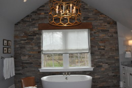 The main point of focus in the master bathroom, also designed by Christopher Patrick, is a floor-to-ceiling stone wall and simple oval-shaped tub. (WTOP/Rachel Nania)