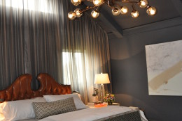 The master bedroom, designed by Christopher Patrick, is both dramatic and calming/cozy at the same time. Patrick used a mix of slate gray, cognac leather and emerald green for the room's color palette. (WTOP/Rachel Nania)