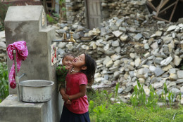 A young girl holding a baby takes a cool drink from a water spigot in the destroyed village of Balua, near the epicenter of Saturday's massive earthquake, in the Gorkha District of Nepal, Thursday, April 30, 2015. (AP Photo/Wally Santana)