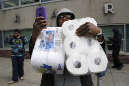 A man holds a cell phone as he carries items, Monday, April 27, 2015, after the funeral of Freddie Gray in Baltimore. Gray died from spinal injuries about a week after he was arrested and transported in a Baltimore Police Department van. (AP Photo/Patrick Semansky)