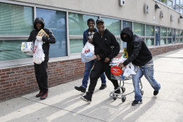 Men carry items, Monday, April 27, 2015, during unrest following the funeral of Freddie Gray in Baltimore. Gray died from spinal injuries about a week after he was arrested and transported in a Baltimore Police Department van. (AP Photo/Patrick Semansky)