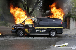 A police vehicle burns, Monday, April 27, 2015, during unrest following the funeral of Freddie Gray in Baltimore. Gray died from spinal injuries about a week after he was arrested and transported in a Baltimore Police Department van. (AP Photo/Patrick Semansky)