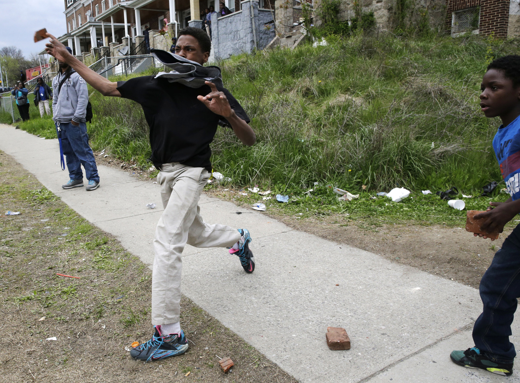 A boy throws a brick at police, Monday, April 27, 2015, during unrest following the funeral of Freddie Gray in Baltimore. Gray died from spinal injuries about a week after he was arrested and transported in a Baltimore Police Department van. (AP Photo/Patrick Semansky)