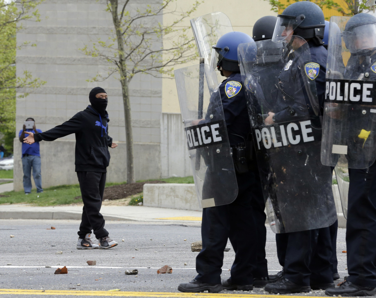 A demonstrator taunts police as they respond to thrown objects, Monday, April 27, 2015, after the funeral of Freddie Gray in Baltimore. Gray died from spinal injuries about a week after he was arrested and transported in a Baltimore Police Department van. (AP Photo/Patrick Semansky)