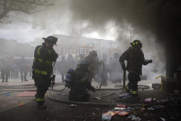 Firefighters prepare to put out a fire at a store, Monday, April 27, 2015, during unrest following the funeral of Freddie Gray in Baltimore. Gray died from spinal injuries about a week after he was arrested and transported in a Baltimore Police Department van. (AP Photo/Patrick Semansky)