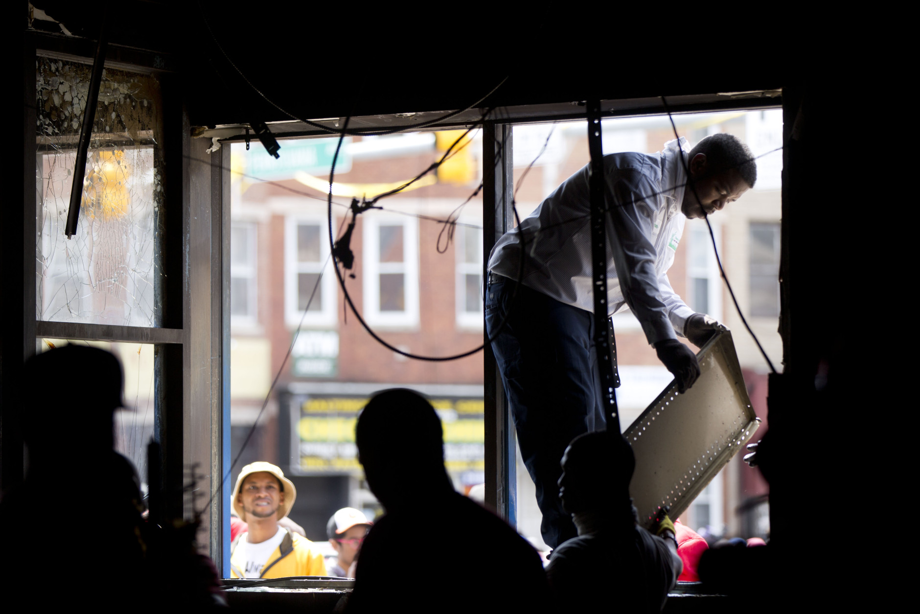 Volunteers clean a CVS pharmacy Tuesday, April 28, 2015, in Baltimore, in the aftermath of rioting following Monday's funeral for Freddie Gray, who died in police custody. Hundreds of volunteers are cleaning up the wreckage left by rioters in the neighborhood where Freddie Gray was arrested. (AP Photo/Matt Rourke)