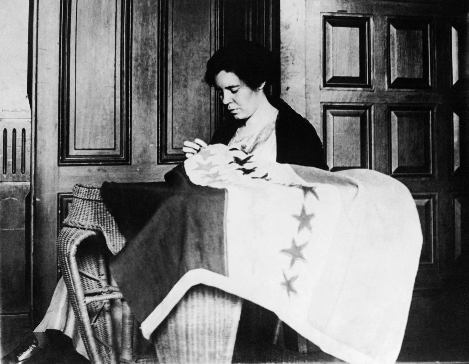 Alice Paul, Chairman of the Nation Women's Party, takes up needle & thread to put the last stitch in the suffrage banner which now has 36 stars representing the 36 states which ratified the suffrage amendment. circa 1932. (AP Photo)