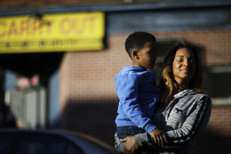 Cierra Powell fights back tears as she holds her son, Keon Lovitt, 6, as they pause to listen to an outdoor church service a block from Monday's riots that followed the funeral for Freddie Gray, who died in police custody, Tuesday, April 28, 2015, in Baltimore. (AP Photo/David Goldman)