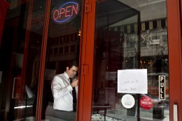 A man checks his cellphone in a restaurant with a sign advertising that the computer is down, as power returns after a brief power outage, Tuesday, April 7, 2015, in Washington. The White House, State Department, and Capitol were all affected by reports of widespread power outages across Washington and its suburbs Tuesday afternoon.  (AP Photo/Jacquelyn Martin)