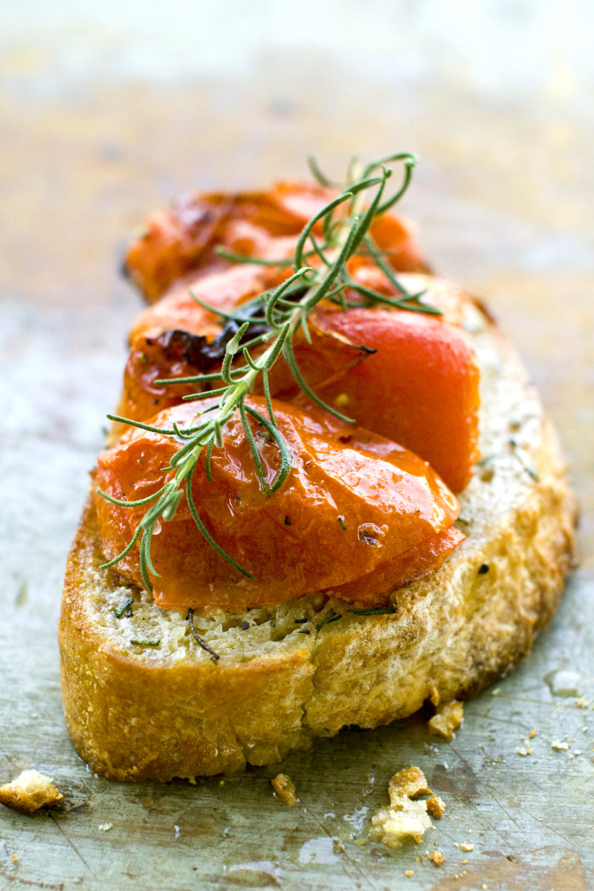 This July 11, 2011 photo shows buttery roasted tomato bruschetta in Concord, N.H.  This bruschetta recipe gets a pat of butter added at the end just before serving.   (AP Photo/Matthew Mead)