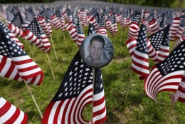 A bbadge with a photograph of Lcpl. Alexander Arredondo is seen attached to a flag in the Massachusetts Military Heroes Fund flag garden on Boston Common in Boston, ahead of Memorial Day, Thursday, May 21 2015. Each of the approximately 37,000 flags represents a Massachusetts military member who died in service from the Revolutionary War to the present. Arredondo is the son of Carlos Arredondo who helped victims at the scene of the Boston Marathon bombings. (AP Photo/Michael Dwyer)