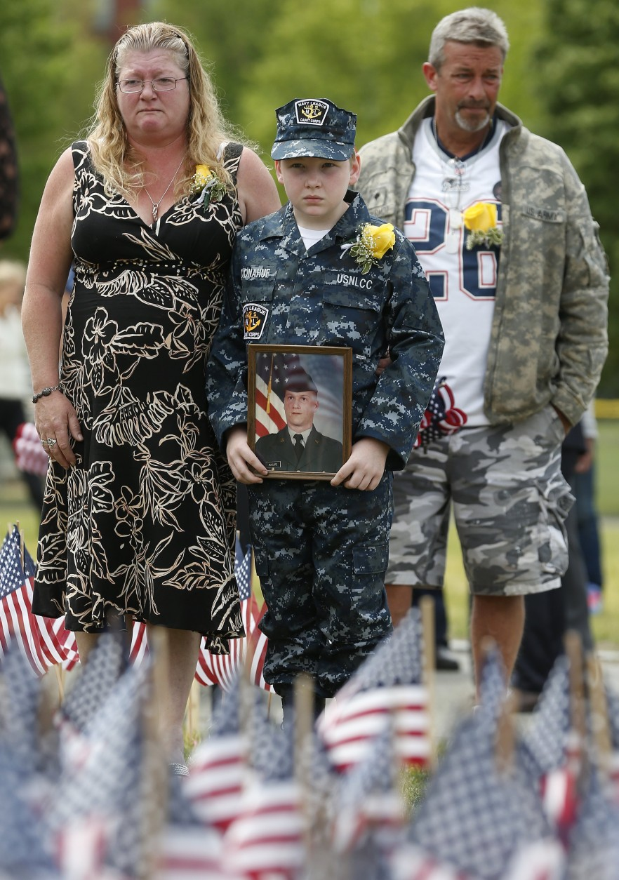 Sharon Maguire, left, stands with her nephew Sean Donahue, center, who holds a picture of his uncle Army Spc. Fred Maguire, and Jeff McDermot,  during a ceremony at the Massachusetts Military Heroes Fund flag garden on Boston Common in Boston, Thursday, May 21 2015. Each of the approximately 37,000 flags placed on the Common for Memorial Day represents a Massachusetts military member who died in service from the Revolutionary War to the present. (AP Photo/Michael Dwyer)