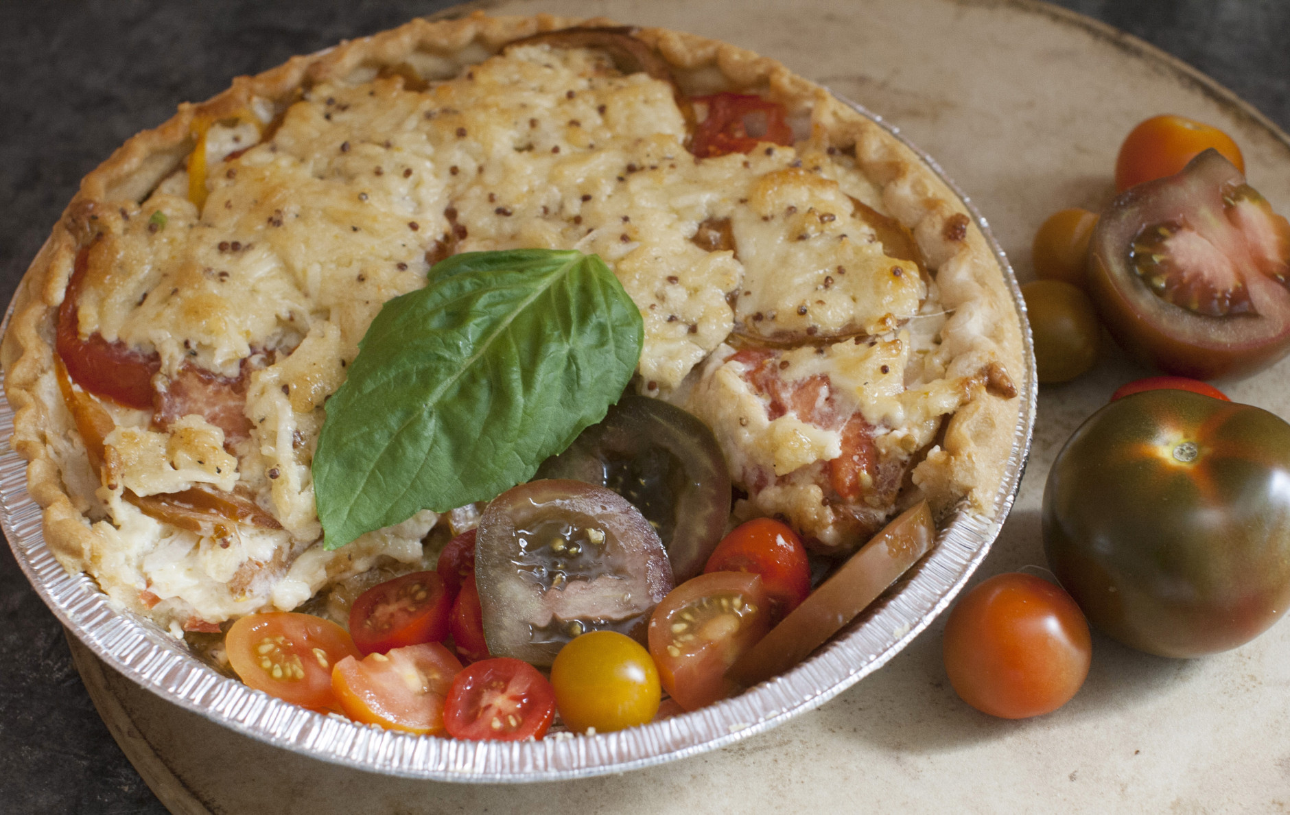 This June 9, 2014 photo shows Dijon tomato and sweet onion pie in Concord, N.H. The Tomato Pie is a classic Southern dish made in summer when the tomato plants are heavy with ripe fruit. (AP Photo/Matthew Mead)