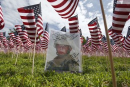 A photograph of Lcpl. Shayne Cabino is seen amongst the flags in the Massachusetts Military Heroes Fund flag garden on Boston Common in Boston, ahead of Memorial Day, Thursday, May 21 2015. Each of the approximately 37,000 flags represents a Massachusetts military member who died in service from the Revolutionary War to the present. (AP Photo/Michael Dwyer)