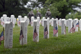 """Members of the 3rd U.S. Infantry Regiment (The Old Guard) place a flag in front of each headstone at Arlington National Cemetery in Arlington, Va., Thursday, May 21, 2015. """"Flags In"""" is an annual tradition that is reserved for The Old Guard since its designation as the Army's official ceremonial unit in 1948. They conduct the mission annually at Arlington National Cemetery and the U.S. Soldiers' and Airmen's Home National Cemetery prior to Memorial Day to honor the nation's fallen military heroes. (AP Photo/Susan Walsh)"""