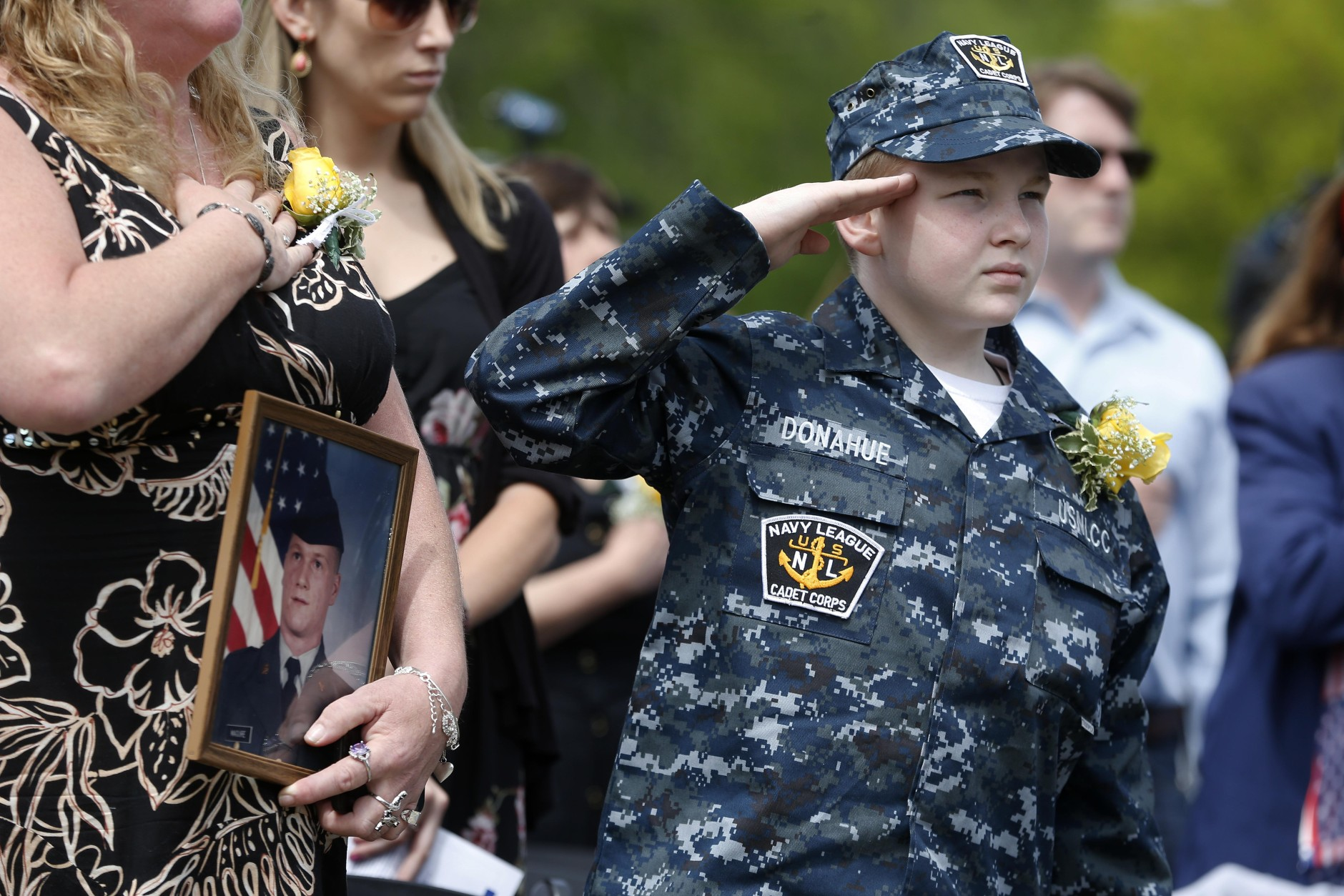 Sharon Maguire, left, of Tewksbury, Mass., holds a picture of her brother Army Spc. Fred Maguire, while standing with her nephew Sean Donahue, right, during the playing of the national anthem at the Massachusetts Military Heroes Fund flag garden on Boston Common in Boston, Thursday, May 21 2015. The fund places approximately 37,000 flags on the Common for Memorial Day to represent the Massachusetts military members who died in service from the Revolutionary War to the present. (AP Photo/Michael Dwyer)