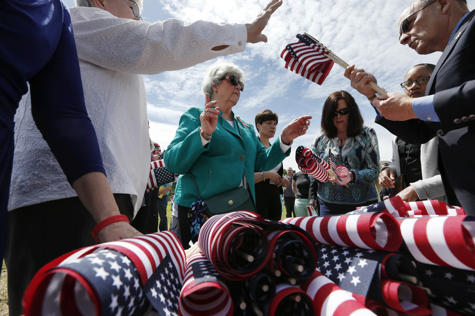 Judy Anderson, center, of North Attleborough, Mass., distributes flags to be placed in the Massachusetts Military Heroes Fund flag garden on Boston Common in Boston, Thursday, May 21 2015. The fund places approximately 37,000 flags on the Common for Memorial Day to represent the Massachusetts military members who died in service from the Revolutionary War to the present. (AP Photo/Michael Dwyer)