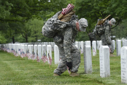 """Third U.S. Infantry Regiment (The Old Guard) Pfc. Benjamin Feldbush of Stafford County, Va., places a flag in front of a headstone at Arlington National Cemetery in Arlington, Va., Thursday, May 21, 2015. """"Flags In"""" is an annual tradition that is reserved for The Old Guard since its designation as the Army's official ceremonial unit in 1948. They conduct the mission annually at Arlington National Cemetery and the U.S. Soldiers' and Airmen's Home National Cemetery prior to Memorial Day to honor our nation's fallen military heroes. (AP Photo/Susan Walsh)"""