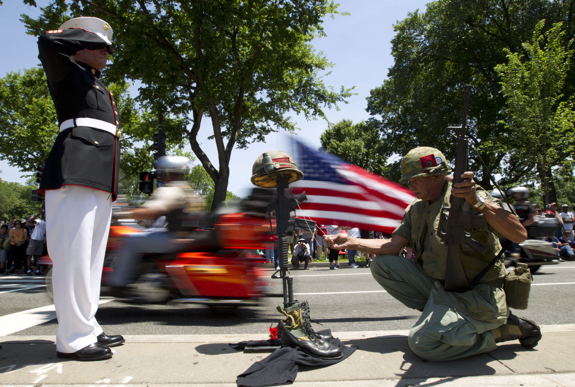 Marine Tim Chamber and Army Eric Cantu salutes as motorcycles drive past during the annual Rolling Thunder parade ahead of Memorial Day in Washington, Sunday, May 24, 2015. (AP Photo/Jose Luis Magana)
